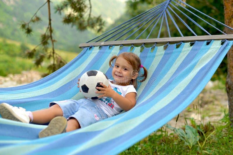 Een klein meisje ligt in een hangmat met een bal en glimlacht stock foto
