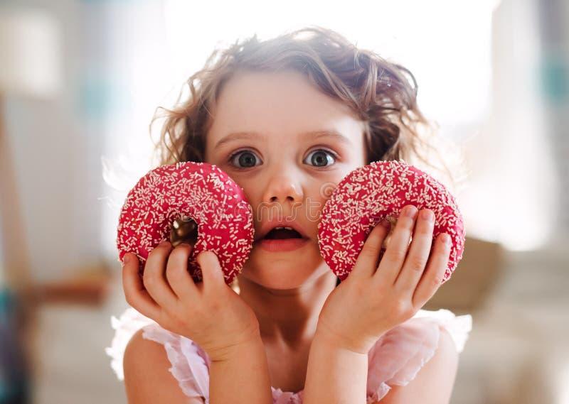 Een klein meisje met doughnuts die thuis, camera bekijken stock fotografie