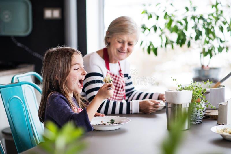 Een klein meisje met grootmoeder thuis stock afbeeldingen