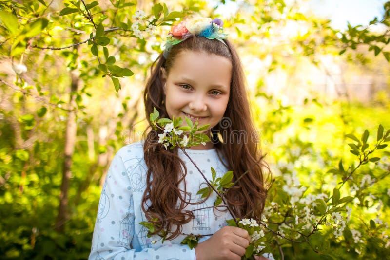 Een klein meisje met een kroon vooraan en een boeket in haar handen op een open plek stock fotografie