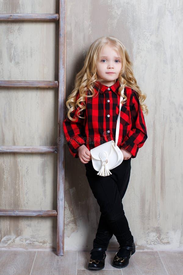 Een klein meisje met licht krullend haar op een grijze achtergrond dichtbij de trapladder royalty-vrije stock foto