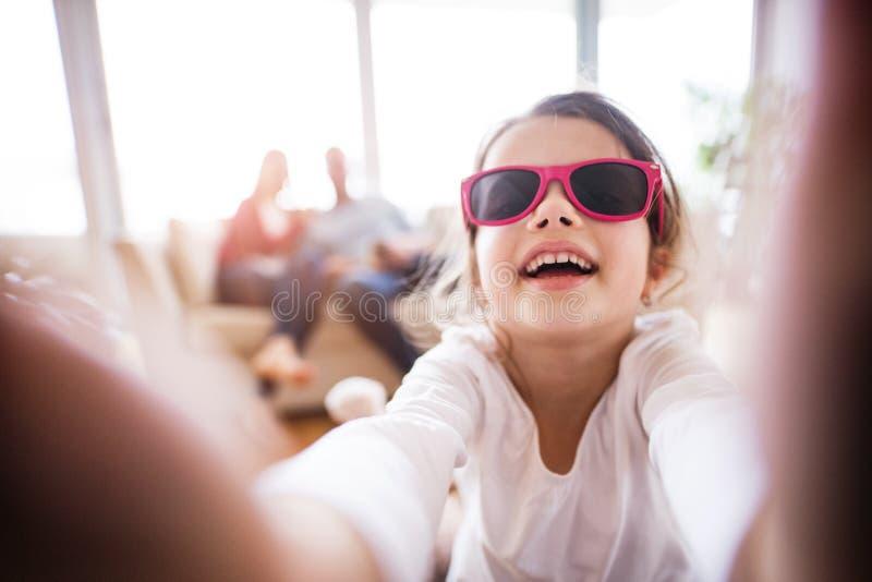 Een klein meisje met onherkenbare ouders die selfie thuis nemen royalty-vrije stock afbeeldingen