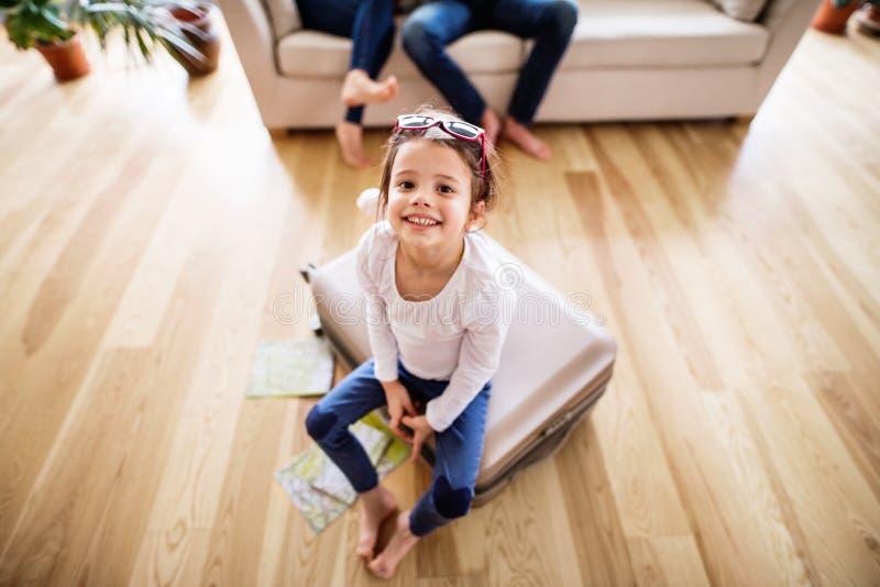 Een klein meisje met onherkenbare ouders die voor een vakantie inpakken stock afbeeldingen