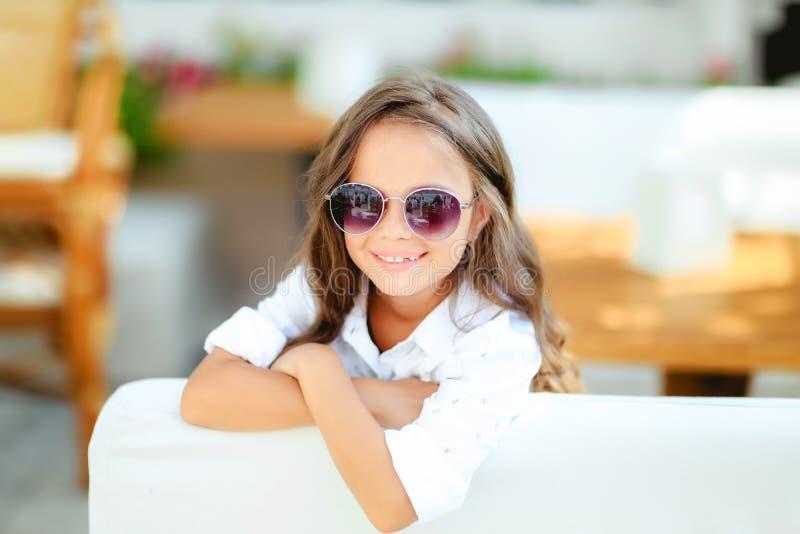 Een klein meisje in modieuze glazen op de terrasachtergrond met lang krullend haar glimlacht voor de camera royalty-vrije stock afbeelding