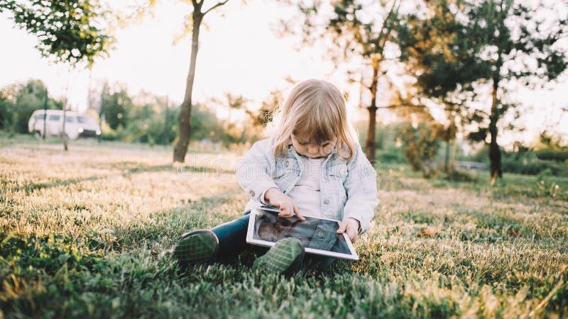 Een klein meisje op het gras stock foto's