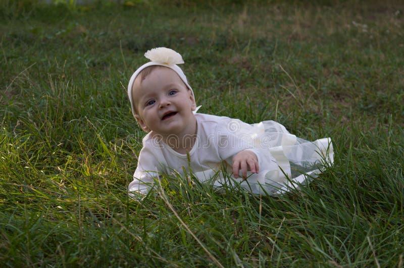 Een klein meisje op het gras stock foto