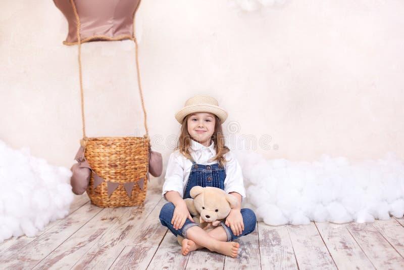 Een klein meisje in overall zit op de vloer met een teddybeer op de achtergrond van een ballon en wolken Het meisje is dreami stock afbeeldingen