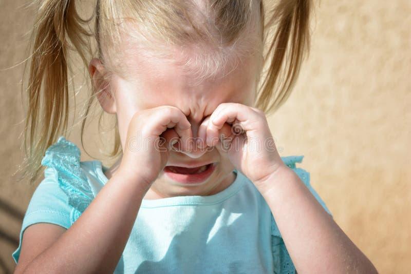 Een klein meisje schreeuwt en wrijft haar ogen met haar handen Kinderen` s hysterie royalty-vrije stock fotografie