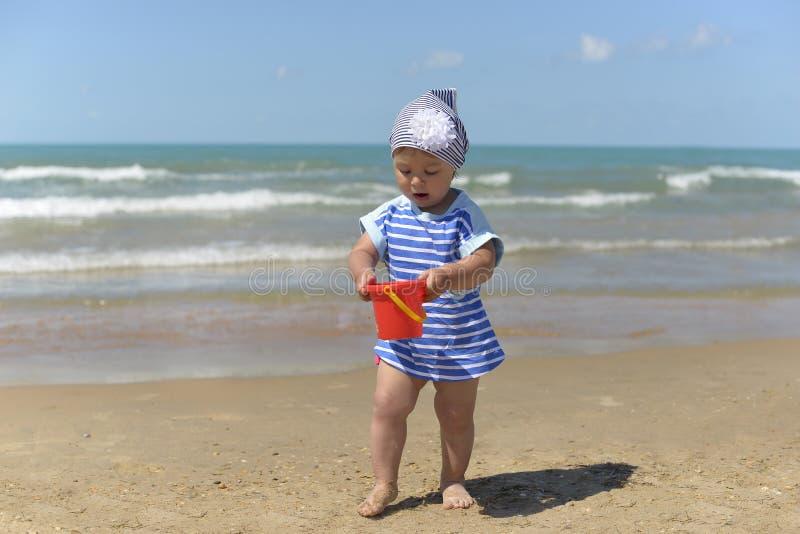 Een klein meisje in sjaal het spelen op het zandige strand stock fotografie