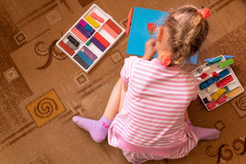 Een klein meisje speelt en beeldhouwt van klei modellering van plasticine en de ontwikkeling van fijne motorvaardigheden stock afbeeldingen
