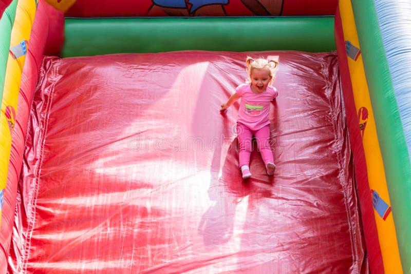 Een klein meisje speelt op een dia in een pretpark stock afbeelding