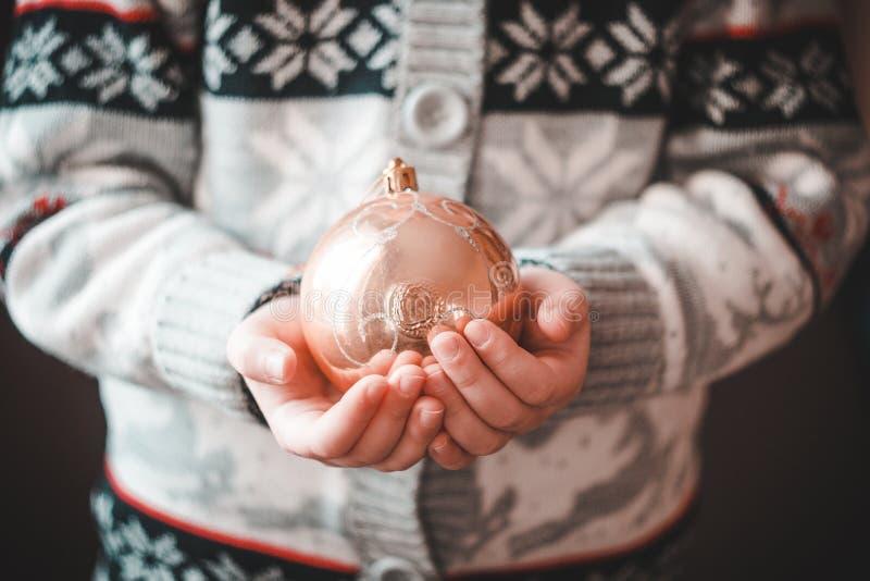 Een klein meisje in een sweater met herten en sneeuwvlokken die de bal van een Nieuwjaar houden royalty-vrije stock afbeeldingen