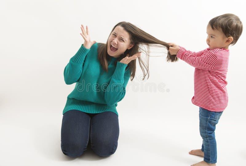 Een klein meisje trekt haar ouder die zusterhaar op wit wordt geïsoleerd royalty-vrije stock foto's