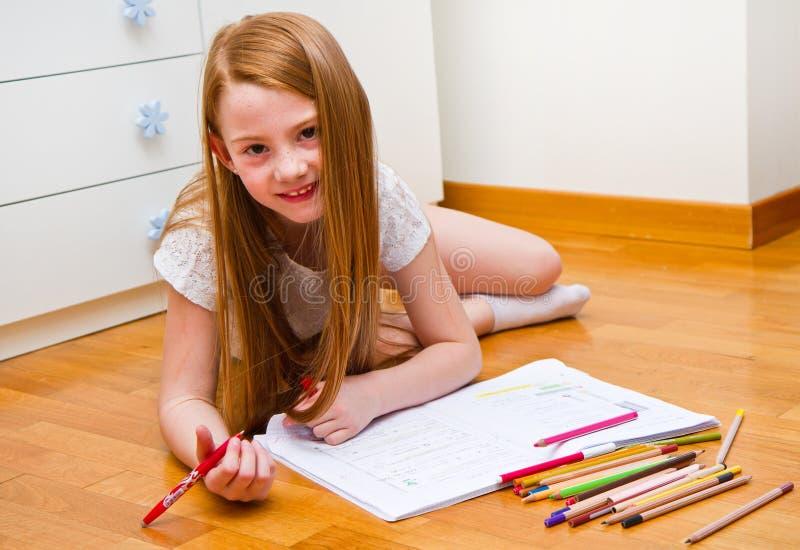 Een klein meisje trekt terwijl leugens op vloer royalty-vrije stock fotografie