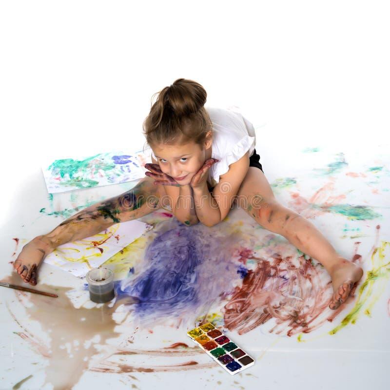 Een klein meisje trekt verven op haar lichaam stock afbeelding