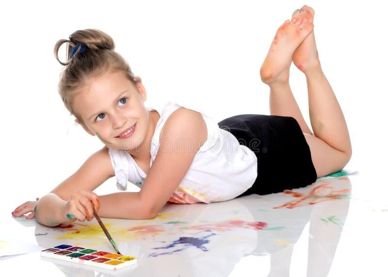 Een klein meisje trekt verven op haar lichaam royalty-vrije stock fotografie