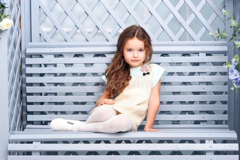 Een klein meisje van zeven met kastanjehaar zit op een houten bank in een grijs-blauwe kleur, glimlachend met heldere kleren en k stock foto's