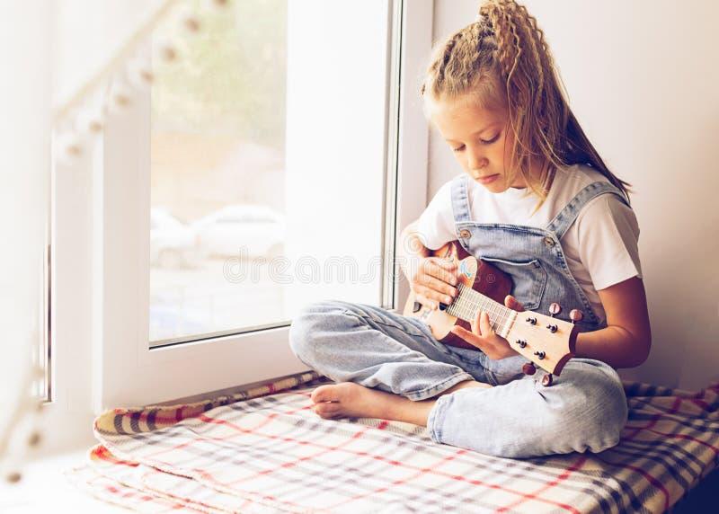 Een klein meisje zit door het venster in het huis spelend de gitaar Selectieve nadruk Het concept muziek en art. stock foto