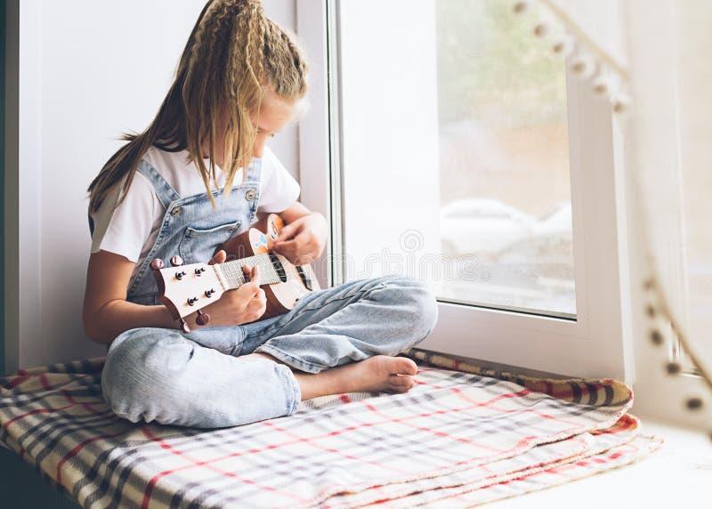 Een klein meisje zit door het venster in het huis spelend de gitaar Selectieve nadruk Het concept muziek en art. royalty-vrije stock afbeeldingen