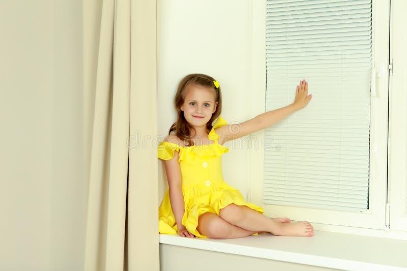 Een klein meisje zit door het venster met jaloezie royalty-vrije stock afbeelding