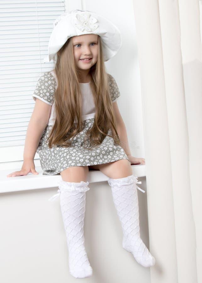 Een klein meisje zit door het venster met jaloezie royalty-vrije stock afbeeldingen