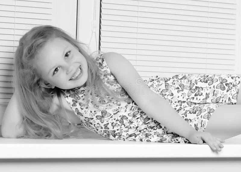 Een klein meisje zit door het venster met jaloezie royalty-vrije stock foto's