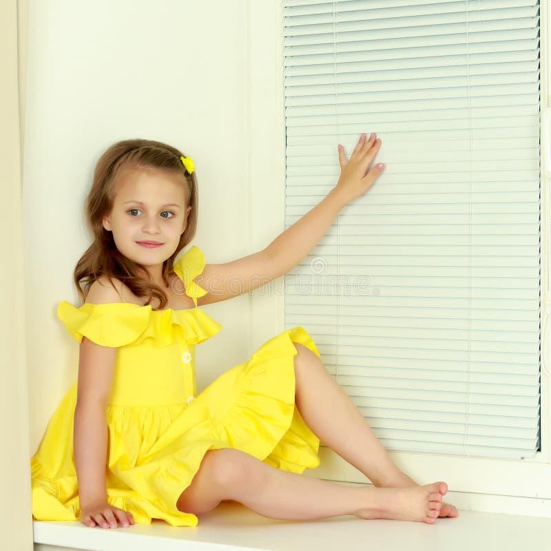 Een klein meisje zit door het venster met jaloezie royalty-vrije stock foto