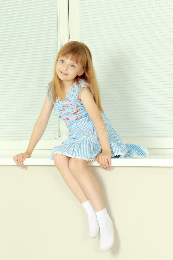Een klein meisje zit door het venster met jaloezie stock foto's