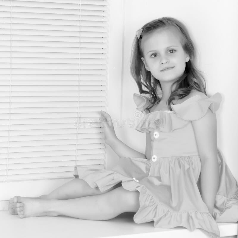 Een klein meisje zit door het venster met jaloezie stock afbeeldingen