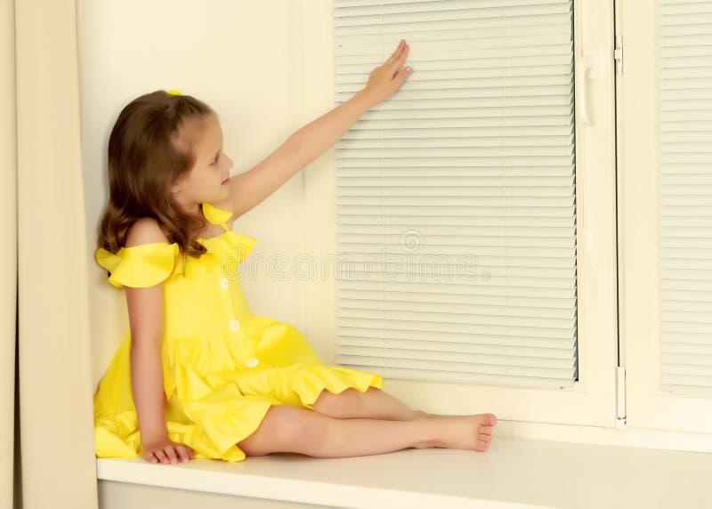 Een klein meisje zit door het venster met jaloezie stock fotografie