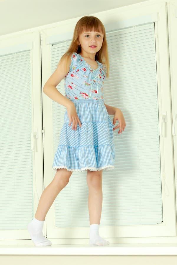 Een klein meisje zit door het venster met jaloezie royalty-vrije stock fotografie