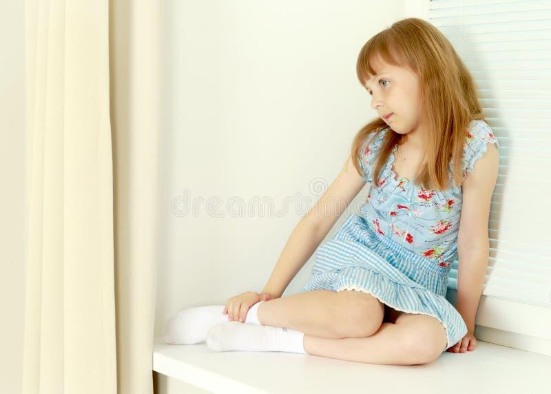 Een klein meisje zit door het venster met jaloezie stock afbeelding