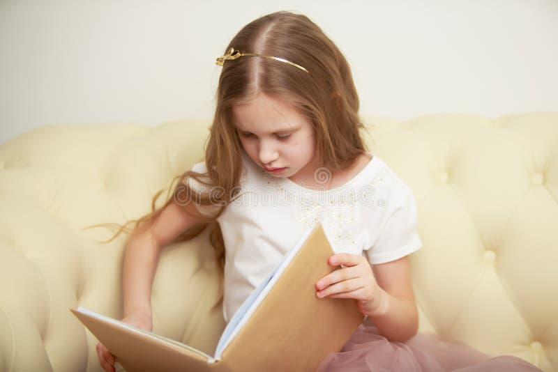 Een klein meisje zit op de laag en leest een boek stock fotografie