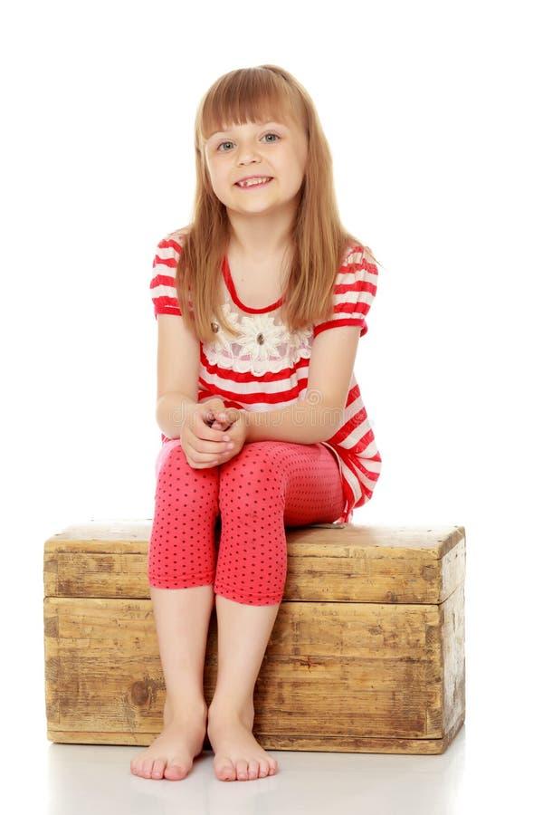 Een klein meisje zit op een houten doos royalty-vrije stock afbeelding