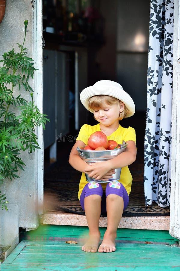 Een klein, mooi meisje in een hoed verzamelde een oogst van rijpe rode tom royalty-vrije stock afbeelding