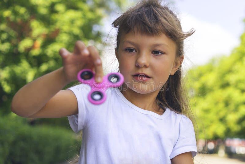 Een klein mooi meisje in een witte T-shirt is weerzinwekkend en voorzichtig houdend een roze spinner in haar hand op de straat royalty-vrije stock foto's