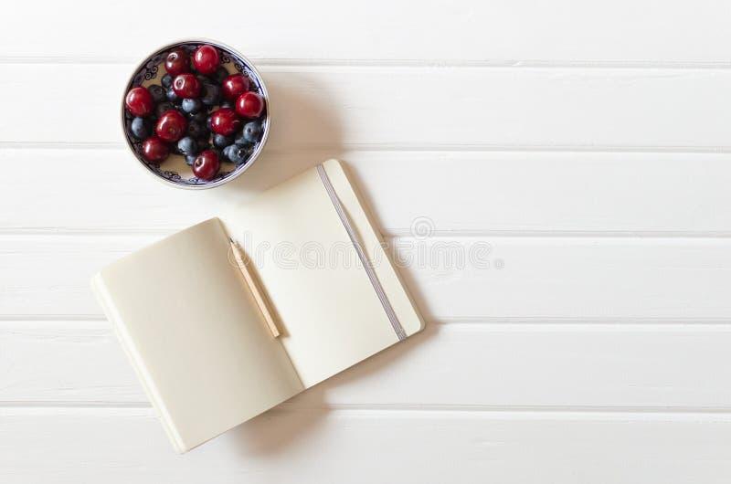 Een klein open notitieboekje met potlood met kom met kersen en bosbessen op de witte houten bureauachtergrond Hoogste mening Vlak stock foto's