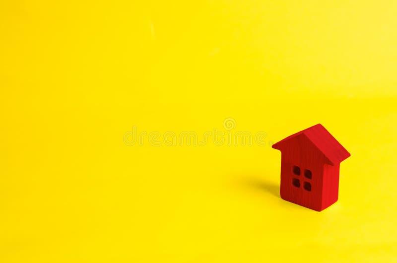 Een klein rood blokhuis bevindt zich op een gele achtergrond Het concept het kopen en onroerende goederen verkopen, het huren Zoe royalty-vrije stock foto's