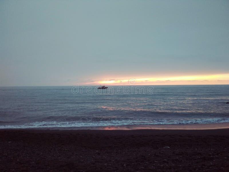 Een klein schip in een kalme overzees bij zonsondergang royalty-vrije stock afbeelding