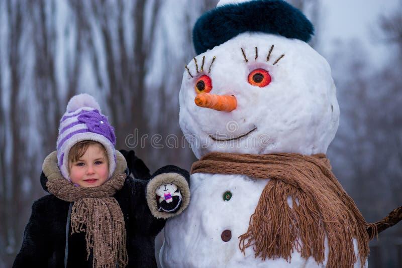 Een klein vrolijk meisje dichtbij grote grappige sneeuwman stock fotografie
