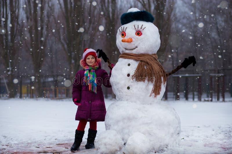 Een klein vrolijk meisje dichtbij grote grappige sneeuwman royalty-vrije stock foto