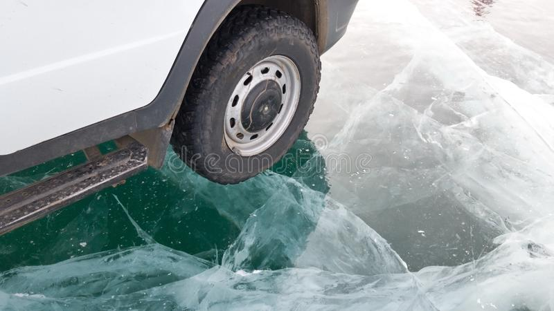 Een klein wiel van een oude auto en een deel van de auto die zich op het duidelijke ijs van meer Baikal in strenge vorst bevinden stock foto