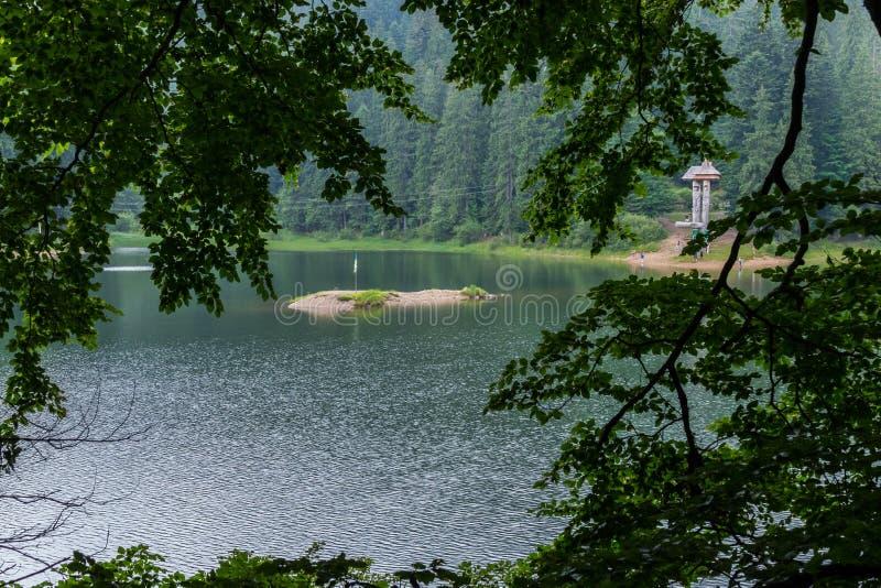 Een klein zandig eilandje met een vlag in het midden van een transparant blauw meer royalty-vrije stock foto's