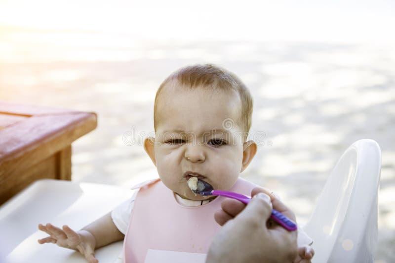 Een kleine baby is boos en wil niet met een lepel eten Het zuigelingsmeisje zit op een stoel op het strand bij zonnige dag stock afbeelding