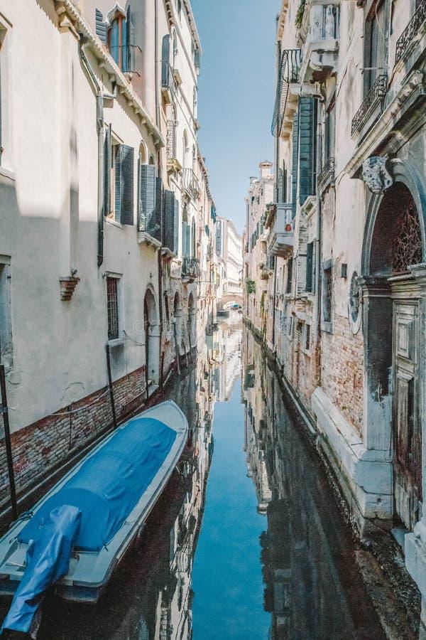 Een kleine blauwe boot bond aan een huis met een bakstenen muur in een smal kanaal, Venetië, Italië royalty-vrije stock afbeelding