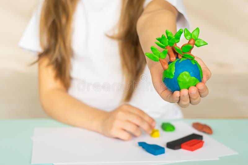 Een kleine bol met bomen in de handen van een kind Lay-out van de planeet van plasticine in de palmen die van kinderen wordt gema stock foto