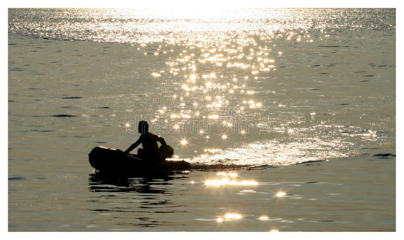 Een kleine boot drijft door het mooie gleaming overzees stock afbeeldingen