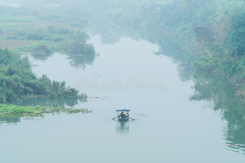 Een kleine boot op Rode Rivier onder Lange Bien-Brug - de winter van 2018 van Hanoi stock foto's