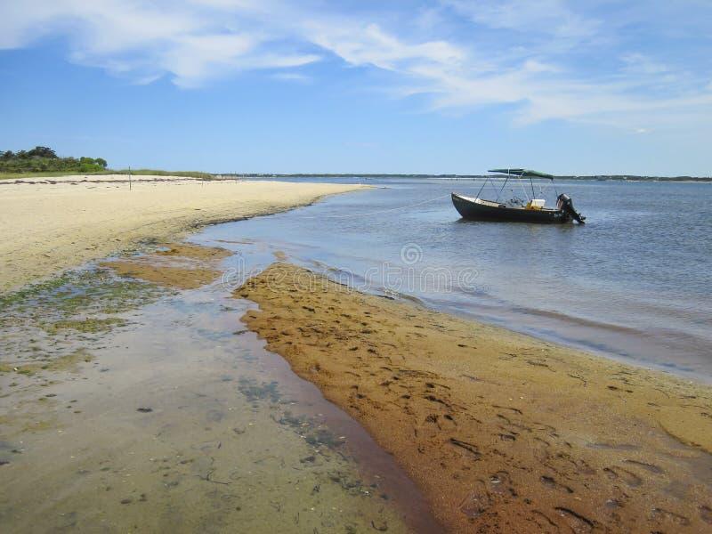 Een kleine boot verankerde op een eenzaam strand stock afbeeldingen