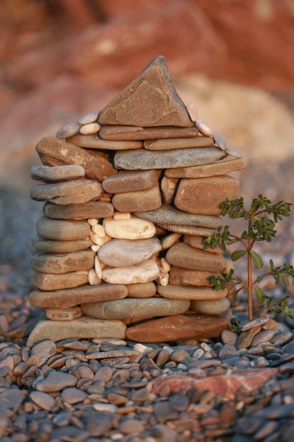 Een kleine bouw van het steenhuis met een boom voor het op strandachtergrond royalty-vrije stock afbeelding